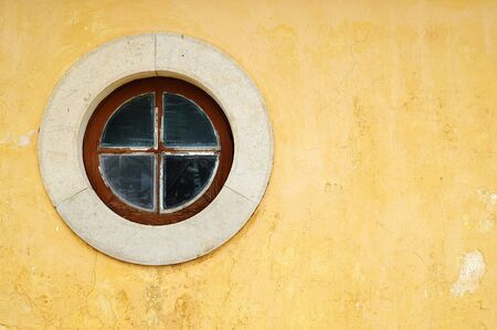 Round wood window with a stone frame on a old yellow wall