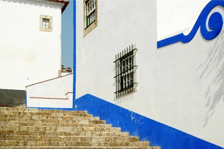 "Detail of a pitoresque wall painted in white and blue at the center of the old medieval town of Ã""bidos, Portugal"