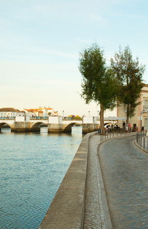 Tavira cityscape from the right bank of the gilao river during a summer sunset. Vertical
