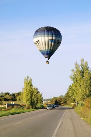 Hot balloon flying over a road with cars Redakční