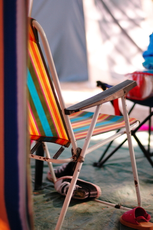 Sun lounger with orange , blue, red and yellow stripes in a camping scene Reklamní fotografie