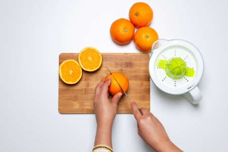 hand chopping a orange in a chop-board and squeezer