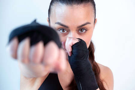 attractive woman looking to the camera with a boxing position punching to the camera