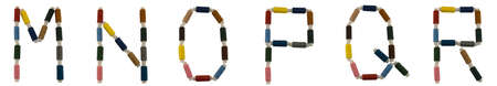 Isolated Font English or Latin alphabet M-R made of colorful spools of thread for sewing