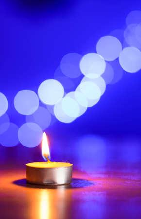 tea candle: Tea candle and a bleu bokeh Stock Photo
