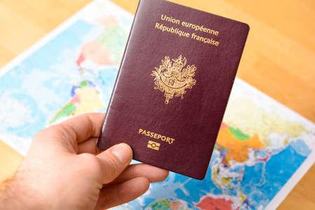バック グラウンドで世界の地図を手にパスポート 写真素材