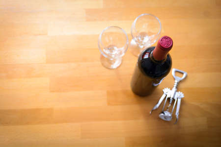 oenology: Bottles of wine with a corkscrew on wood table Stock Photo