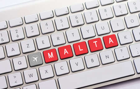 insular: MALTA writing on white keyboard with a aircraft sketch Stock Photo