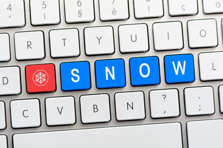 SNOW writing on white keyboard with a snowflake sketch Stock Photo