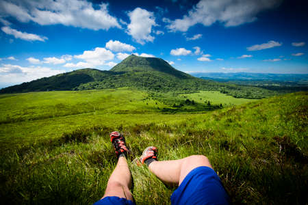 Puy de Dome mountain and hikers legs, Auvergne, France Фото со стока