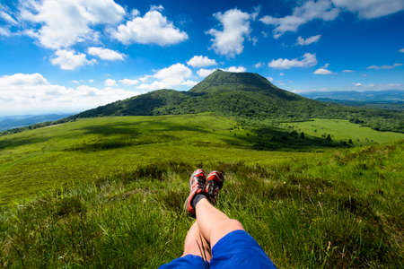 aura: Puy de Dome mountain and hikers legs, Auvergne, France Stock Photo
