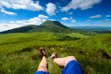 ramble: Puy de Dome mountain and hikers legs, Auvergne, France Stock Photo