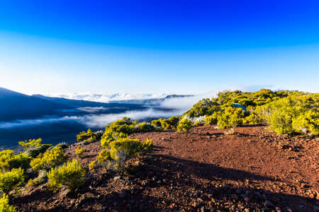 Landscape with cliffs of the volcanic area at Reunion Island with a blue sky