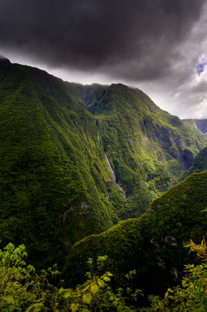 Waterfall and cloudy landscape at Takamaka Valley, Reunion Island