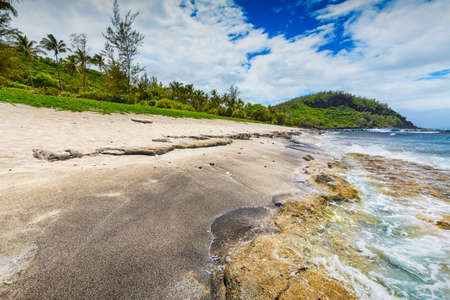 Sunny day with rocks, waves and sand at Grande Anse Beach, Reunion Island
