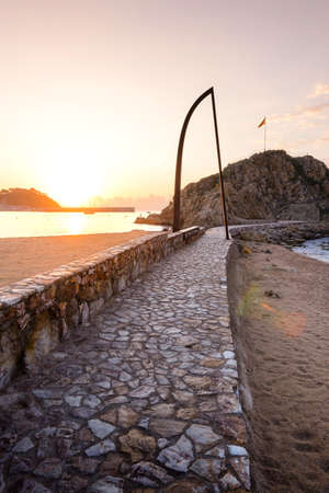 Sunrise over Blanes beach and view of Sa Palomera rock in Spain Фото со стока