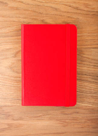 elastic band: Red copybook with elastic band on wooden
