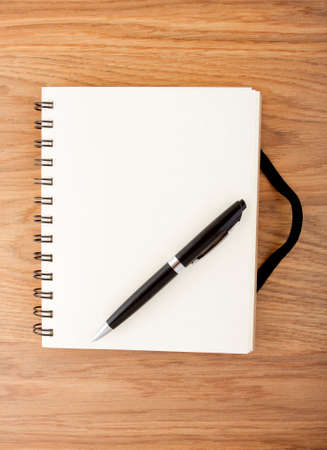 elastic band: Recycled paper notebook with black elastic band and pen on a table