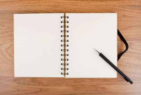 elastic band: Opened notebook with black elastic band and pencil on a table.