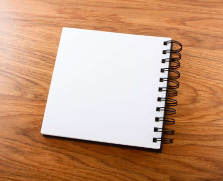 Notepad with a spiral binding on a wooden photo