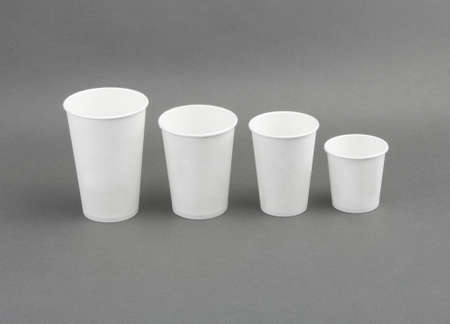Coffee drinking cup sizes. Paper coffee cup on a grey background photo