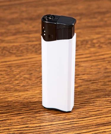 White lighter on wooden background photo