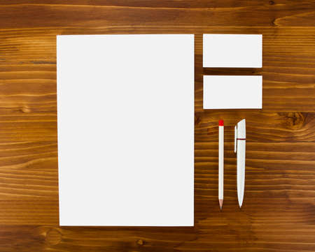 consist: Blank Stationery on wooden background. Consist of Business cards, A4 letterheads, pen and pencil