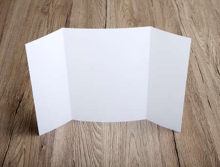 handouts: Blank gate fold brochure on wooden background to replace your design Stock Photo