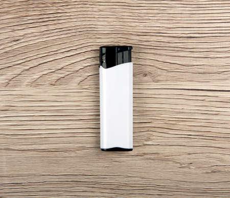 gas lighter: White lighter on a wooden background