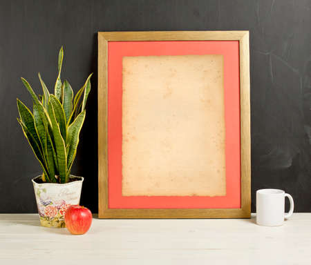 contemporary living room: Mock up of blank photo frame with plant pot, mug and apple on wooden shelf