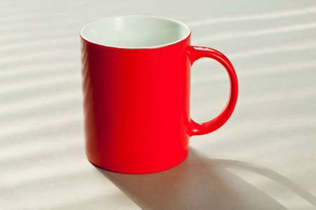 Red empty mug standing on a grey table