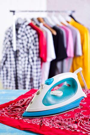 Iron on ironing board on home interior background Stock Photo