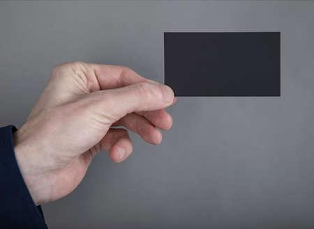 A man in a blue shirt holding a black business card