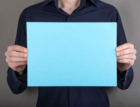 A man in a blue shirt holding a blue letterhead