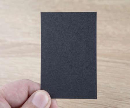 A man holding a black business card
