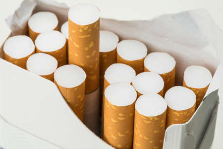 Open pack of cigarettes on white background.