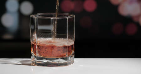 Pouring whiskey drink into glass on dark background.