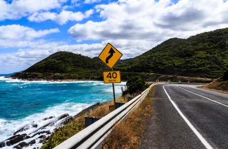sky is the limit: The yellow bend and 40 km h speed limit signs on the great ocean road in Victoria,Australia