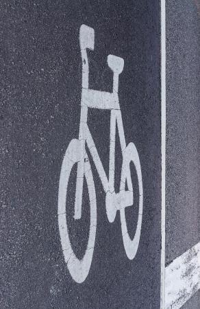 White bicycle lane sign on the tarmac street photo