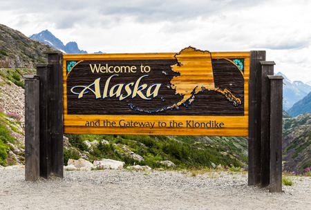 welcome sign: The Welcome to Alaska and the Gateway to the Klondlike sign in Alaska, America in the cloudy day