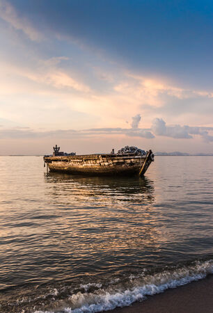 The old and big boat on the sea in Pattaya, Thailand at sunset photo
