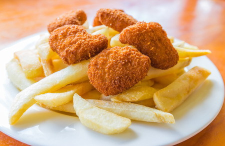 The deep fried potato chips and chicken nuggets on the white dish with the wooden table photo