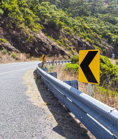 trip hazard sign: The yellow curve road sign on the great ocean road in Victoria,Australia
