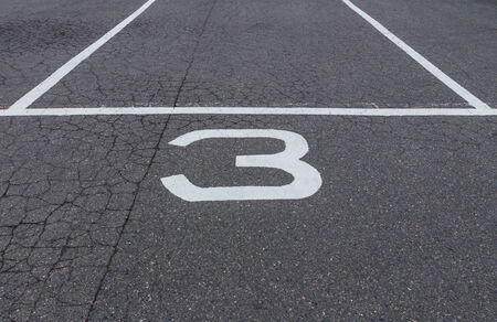 The white number three bus park sign on the tarmac street photo