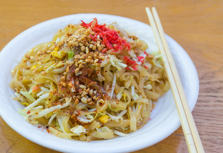 Fried noodles Pad Thai with the white dish on the wooden table photo