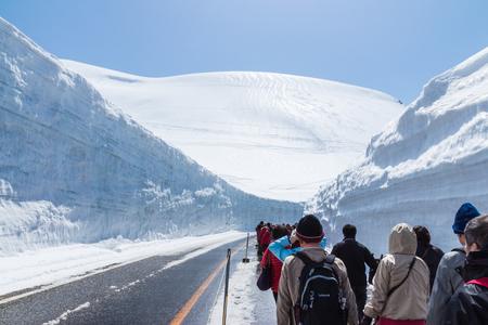 TATEYAMA, JAPAN - MAY 10, 2014: Unidentified tourists walk along snow corridor on Tateyama Kurobe Alpine Route, Japanese Alp in Tateyama, Japan Editorial