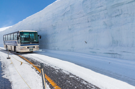 TATEYAMA, JAPAN - MAY 10, 2014: The bus move along snow corridor on Tateyama Kurobe Alpine Route, Japanese Alp in Tateyama, Japan