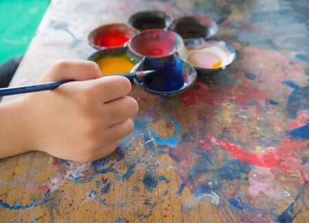 artist: The kids hand holding paintbrush with the watercolor palette on the wooden table Stock Photo