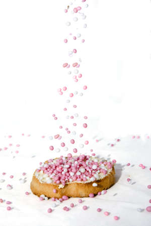 A biscuit is sprinkled with sweets on a white background.