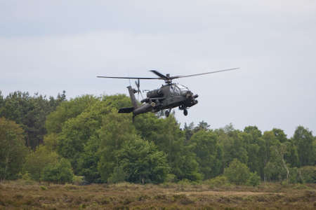 A apache helicopter is hoovering above the ground.